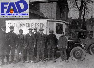 """Deze week een foto uit 1921 van een der oudste fabrieken uit Cuijk. Brouwerij Cevelum bestaat al ruim 100 jaren. Ongeveer op de parkeerplaats van Maartenshof is de heer Petrus Toonen in 1896 begonnen met brouwerij ëDe Ster'. Zijn zoon Franciscus heeft later deze brouwerij overgenomen. Deze ging in 1921 een vennootschap aan met brouwer Barten uit Beugen. Er werd een nieuwe brouwerij gebouwd aan de Kaneelstraat met de nieuwe naam """"Cevelumî, wat de oude Romeinse naam van Cuijk is. Het Cevelumbier stond hoog aangeschreven en werd meerdere malen bekroond zowel in Parijs als in Pilzen. (Tsjecho-Slowakije) In de twee wereldoorlog brandden de brouwerij en het woonhuis geheel af. Deze werden na de oorlog weer herbouwd. Bijna al de kleine brouwerijen werden door de grote opgekocht, en moesten van de markt verdwijnen. Ook de Cuijkse brouwerij ontkwam niet aan dit lot, en werd opgekocht door """"De Oranjeboomî. (Skol) Tegenwoordig kennen wij Cevelum als groothandel in dranken en natuurlijk slijterij Cevelum op het Louis Jansenplein. Op deze foto uit 1921 staan van links naar rechts; Hent Raafs, Jan Raafs, van Tits uit Beugen, Nˆlleke Heijl, Fr.Toonen, (de brouwer) Jan Peters, Barten uit Beugen, Harry Toonen uit Oeffelt. Achter het stuur van"""